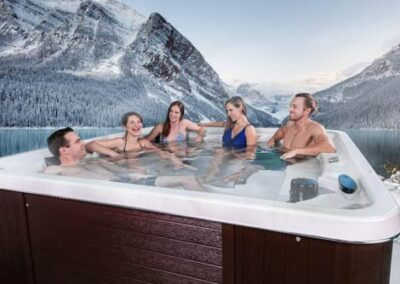 Friends enjoying an Arctic Spas hot tub in mountains in winter